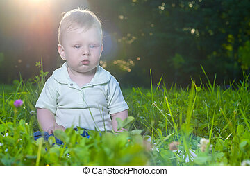 Portrait of Little Cute Caucasian Toddler Child Sitting on Grass Outdoors