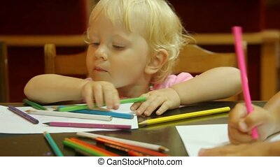 portrait of little cute girl drawing pencils on white paper