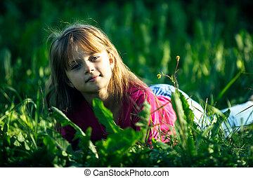 Portrait of little cute girl in the green grass.