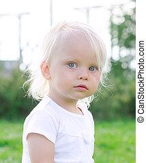 Portrait of little cute girl in the park
