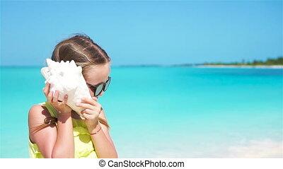 Portrait of little cute girl listening a big seashell on the beach. Slow motion