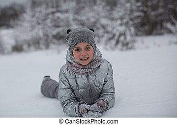 Portrait of little cute girl playing in the winter outdoors.
