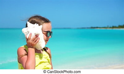 Portrait of little cute girl with a big seashell background the sea