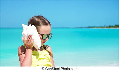 Portrait of little cute girl with a big seashell