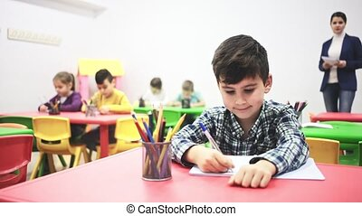 Portrait of little diligent schoolboy writing at lesson in elementary school. High quality FullHD footage