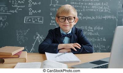 Portrait of little genius in classroom sitting at desk ...
