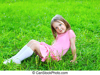 Portrait of little girl child sitting on the grass in sunny summer day