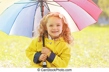 Portrait of little girl child with colorful umbrella in sunny autumn day