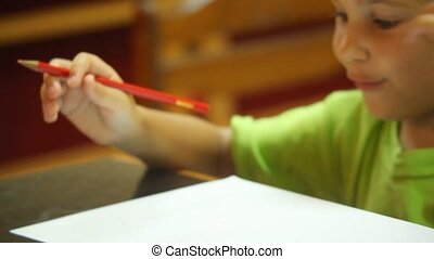 portrait of little girl drawing pencils on white paper, focus on pencil