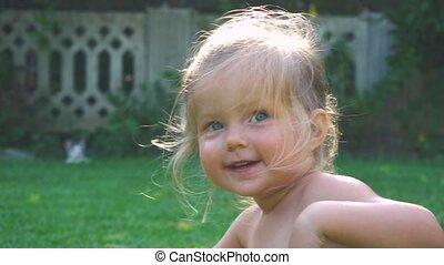 Portrait of little girl having fun on lawn in slow motion -...