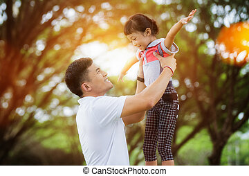 Portrait of little girl hugging her daddy with nature and sunlight