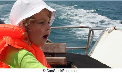 portrait of little girl in life jacket sitting in going cutter looks at sea