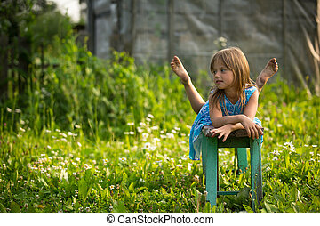Portrait of little girl in the yard of a country house