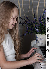 Portrait of little girl in white dress playing piano. Concept of music study and arts