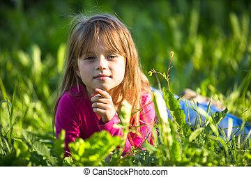 Portrait of little girl lying in the grass.