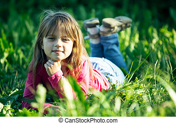 Portrait of little girl lying on a meadow in the grass.