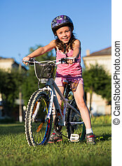 Portrait of little girl on a bicycle in summer park