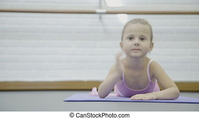 Portrait of little girl on mat, who looks with interest...