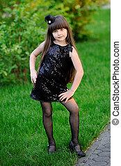 portrait of little girl outdoors in black dress