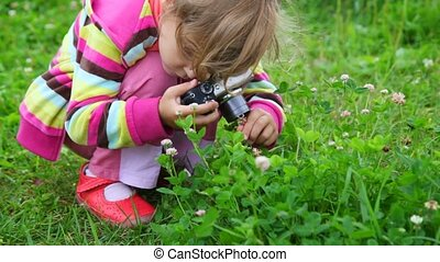 portrait of little girl photographing flower in park