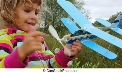 portrait of little girl playing with toy airplane outdoor