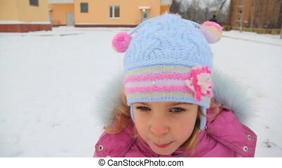portrait of little girl riding on sled in winter city