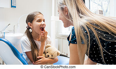 Portrait of little girl showing teeth to her mother after teeth treatment in dentist office