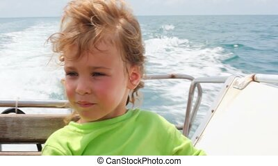 portrait of little girl sitting in going cutter looks at sea