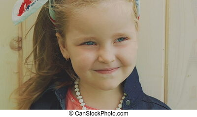 Portrait of little girl with blowing hair smiling at camera indoor. Slowly