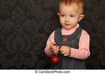 Portrait of little girl with Christmas toy in hands of denim dress. Close-up. Horizontal format.