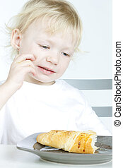 portrait of little girl with croissant