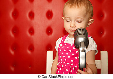 Portrait of little girl with microphone on rack against red...