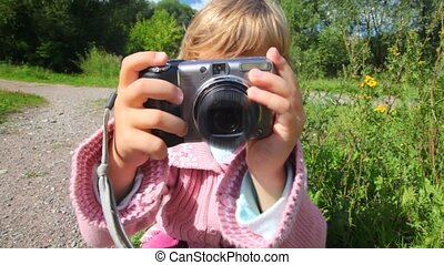portrait of little girl with photo camera in park