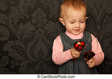 Portrait of little girl with Russian traditional spoons in her hands against ornamental wall.