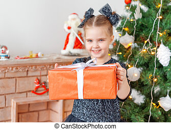 Portrait of little happy cute girl with Christmas present