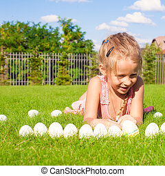 Portrait of little happy girl playing with white Easter eggs on green grass