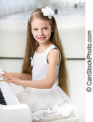 Portrait of little pianist in white dress playing piano