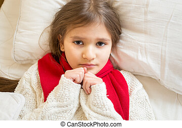 little sad girl in white sweater lying under blanket at bed