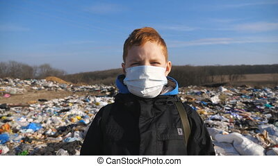 Portrait of little serious boy in medical protective mask stands against the background of dirty garbage dump and looks into camera. Concept of environmental pollution problem. Dolly shot Close up.