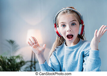 portrait of little shocked girl listening music in headphones