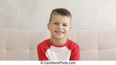 Portrait of little smiling boy is sitting on sofa and looking at camera.