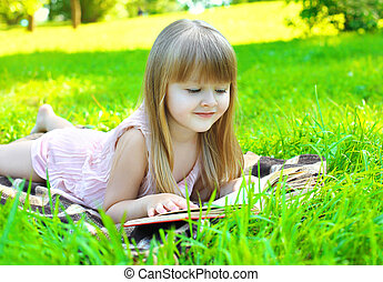 Portrait of little smiling girl child reading a book lying on the grass in sunny summer day