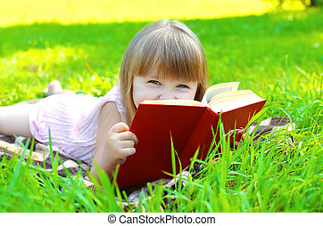 Portrait of little smiling girl child with book lying on the grass in sunny summer day