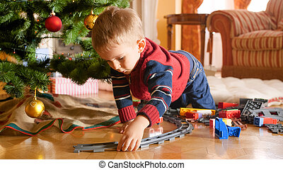 Portrait of little toddler boy building railway and playing with toy train under Christmas tree