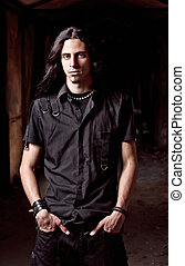 Portrait of long-haired handsome young man in low key - ...