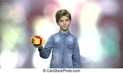 Portrait of lovely child holding gift box.