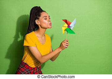 Portrait of lovely funny girl blowing paper propeller mill having fun playing isolated over bright green color background.