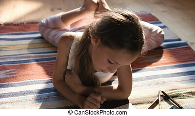 Portrait of lovely girl drawing a picture with colorful pencils on a carpet