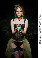Portrait of lovely green fairy. Seductive smiling young girl with glass of absinthe