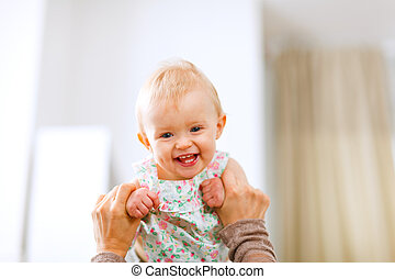 Portrait of lovely laughing baby playing with mother